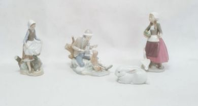 Lladro model of a seated boy with a dog, 19cm high, a Lladro figure of a girl with a basket of