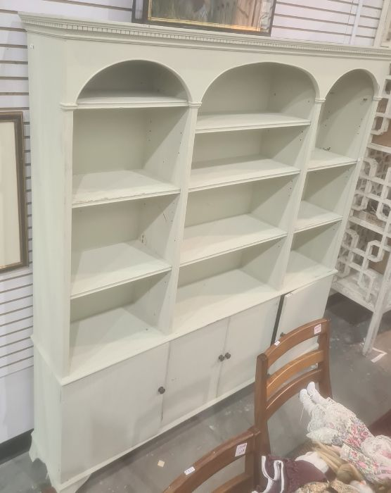 Painted dresser, the moulded cornice above three arches enclosing shelves, four cupboard doors