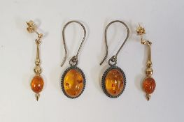 Pair of 9ct gold drop earrings, each set with an oval amber cabochon and a pair of silver and
