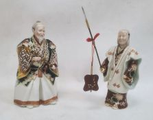 Japanese porcelain figure of a man in robes holding a sword and another figureholding a spear, 24cm
