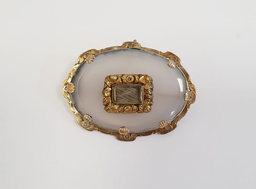 Victorian moonstone and gold-coloured metal mourning brooch, the oval stone bevelled and set with
