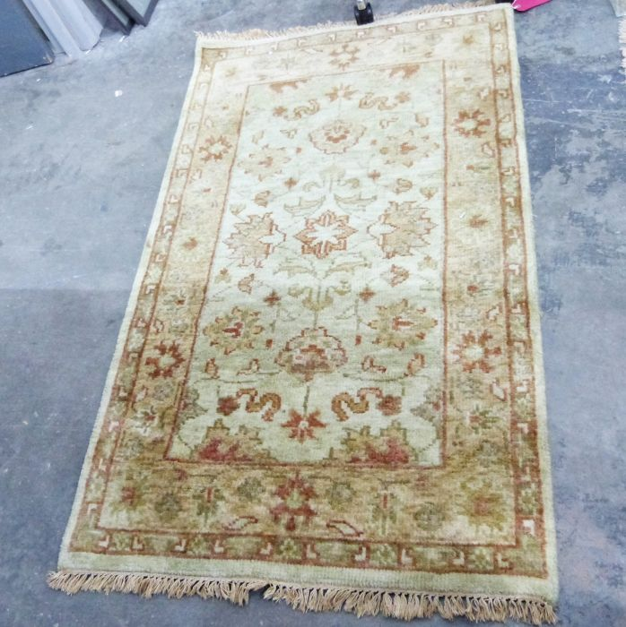 Modern rug in golds and creams with stylised floral central panel and borders 150 x 92cm