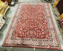 Modern red ground rug with allover foliate decoration, cream ground foliate decorated border,