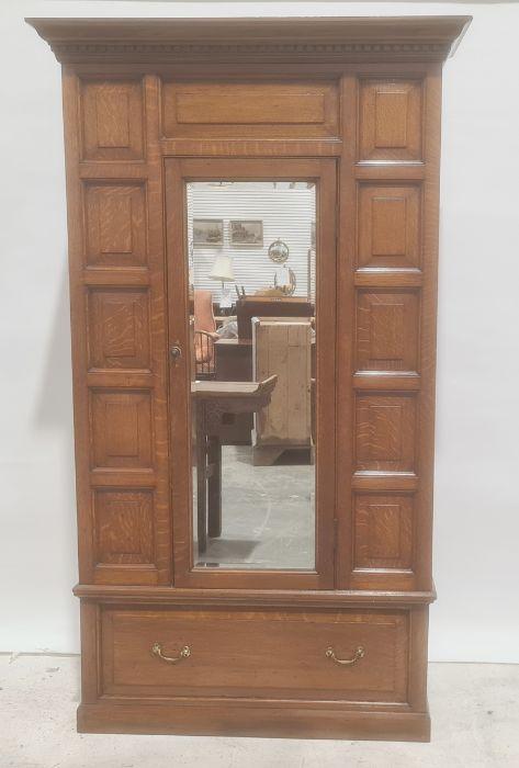 Early 20th century oak single door wardrobe, moulded cornice, panel decoration, mirror to door above