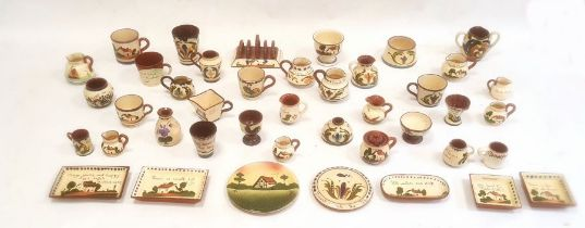 Large quantity of motto ware potteryincluding a toast rack, cups, jugs, egg cups, etc