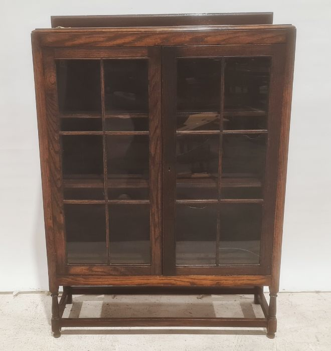 Early 20th century oak bookcase, the astragal glazed doors enclosing shelves, turned and block