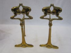 Pair of Art Nouveau brass firedogswith silver-coloured screws, 23.5cm high (2)