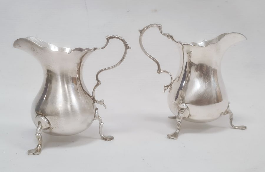 Two similar silver milk jugswith scroll handles, on shaped pad feet, one Birmingham 1959, the other