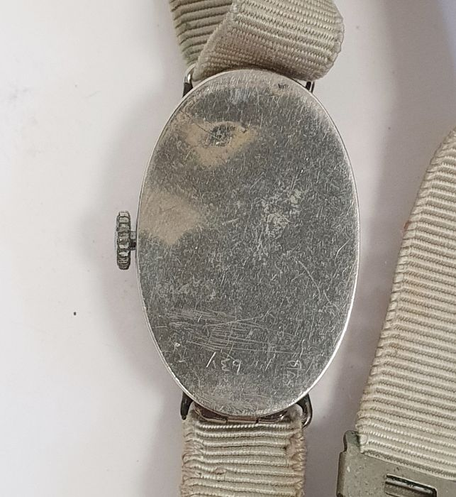 A 1920s platinum and diamond lady's wristwatch on fabric strap, oval with Arabic numerals and an - Image 3 of 10