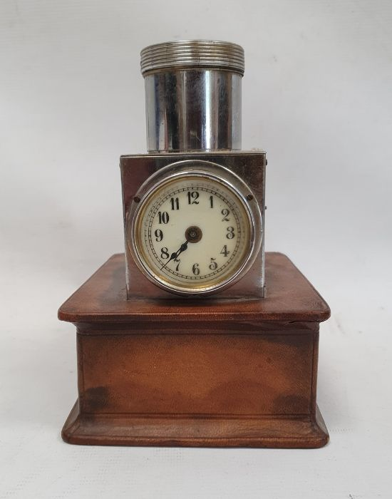 A steel-bodied clock with Arabic numerals to the enamel dial mounted on leatherette covered platform