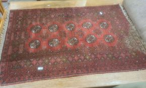 Red ground Eastern-style rug, the central field with ten elephant foot guls, stepped border, 117cm x
