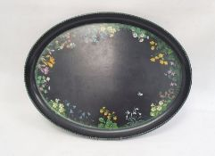 Papiermache tray of oval form, decorated with wild flowers, on a black ground, 51cm long, and two