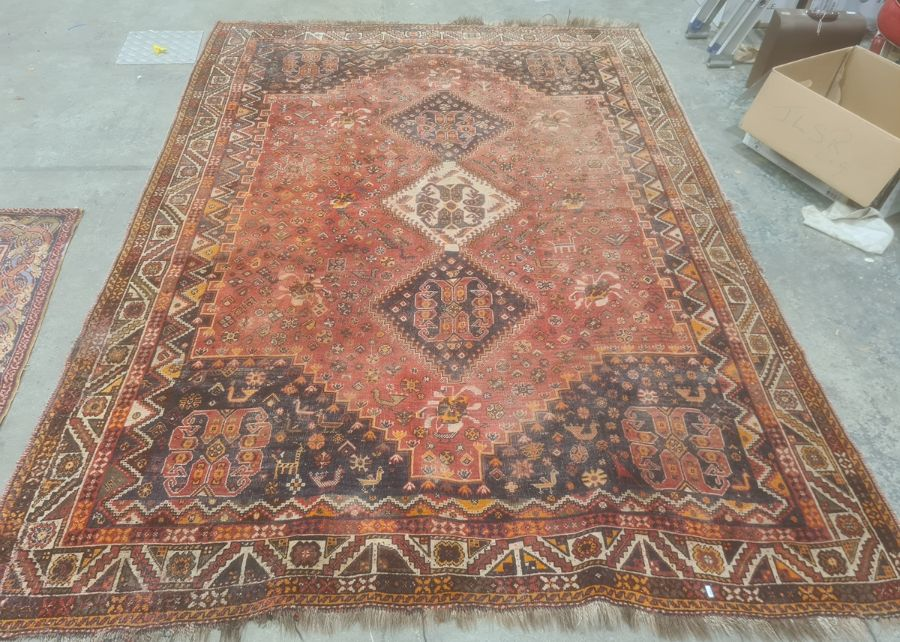 Red ground Eastern rug with three diamond-shaped medallions to the central field, decorated with