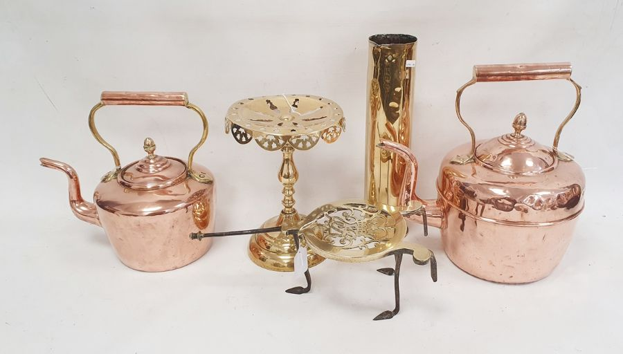 Two copper kettles, a brass trivetwith royal cipher, a set of five graduated copper saucepans
