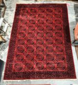 Modern Eastern-style red ground rug, the central field with elephant foot guls, stepped border