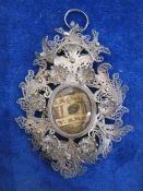 Victorian silver filigree reliquary pendantwith central oval glass enclosing writing on paper