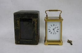 Brass and glass carriage clockwith Roman numerals to the dial, in leather carry case