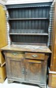 20th century oak Arts & Crafts-style dresser, the rack with moulded cornice above two shelves, the