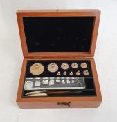 Graduated set of brass cylindrical weightsup to 100g, with tweezers, in mahogany case, 14cm wide