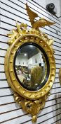 19th century circular wall mirrorsurmounted by eagle, with a carved giltwood frame, the convex