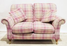Modern two-seater sofa in pink tartan upholstery, on turned supports to brass caps and castors