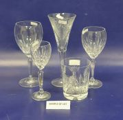 Four Waterford cut tumblers, oval medallion and bow decorated, five matching flared champagne flutes