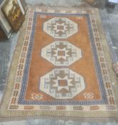 Eastern style rug with terracotta ground, central field with three repeating cream ground hooked