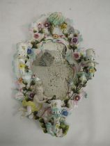 19th century porcelain wall mirrorwith three candle sconces, floral encrusted decoration and relief