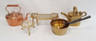 Two brass trivets, a brass watering can, a copper kettle and two brass saucepans