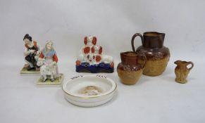 Three stoneware jugs, Staffordshire flatware spaniel group, pair of figuresand a baby plate'HRH