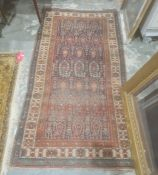Eastern rug with blue ground central field with hooked repeating medallions, stepped border, 196cm x