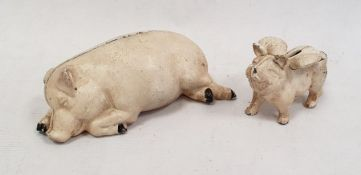 Cream painted cast iron pig money box thepig lying down and anothersmaller, the pig with wings (2)
