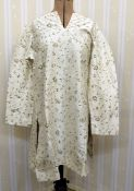Kaftan-style silk dressembroidered with flowers in cream and grey, a purple satin dresswith
