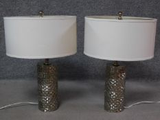 A pair of cylindrical textured metal table lamps with cross hatched design. H.60cm