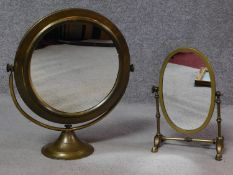Two Edwardian brass framed swing toilet mirrors. One oval on a four footed linear stand the other
