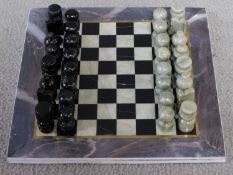 A vintage boxed Turkish carved hardstone chessboard and pieces. The pieces are made from a pale
