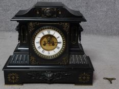 A large Victorian craved black slate mantel clock by Junghans. With engraved gilded foliate