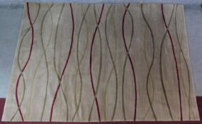 A contemporary 'Rug Company' carpet with intertwined bands on a beige field 192x277cm