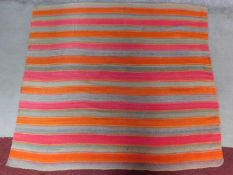 A contemporary linear rug with repeating orange and pink stripes on a grey field 180x200cm