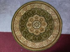 A circular Eastern rug with central pendant medallion on a green and ivory field 150x150cm