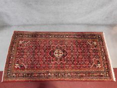 A Hosseinabad rug with central pendant medallion on a rouge field with repeating floral motifs