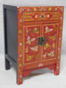 A Chinese red lacquered side cabinet with allover butterfly decoration. H.60 W.40 D.32cm