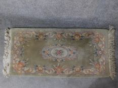 A Chinese rug with central floral medallion set on a pastel field within floral borders 144x63cm