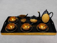 A 20th century gilded black lacquer ceremonial Japanese tea set on gilded tray. It has a moulded