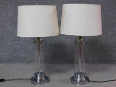 A pair of glass and polished chrome column table lamps with round bases. H.72cm