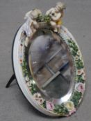 A 19th century Sitzendorf style oval shaped porcelain dressing mirror with relief flower and