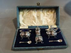 A Walker and Hall cased sterling silver cruet set. The mustard and salt pots have blue glass liners.