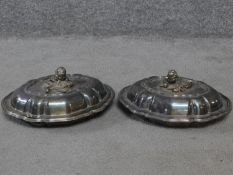 A pair of antique silver plated lidded warming dishes. With floral form and foliate sculpted