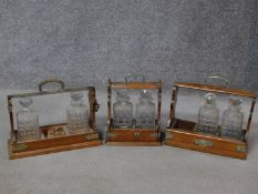 Three miscellaneous oak decanter tantaluses. (Two decanters missing)