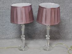 A pair of contemporary clear perspex table lamps with blush pleated shades. H.61cm